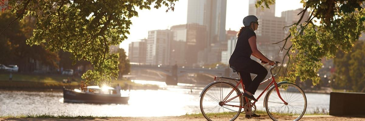 Female cyclist riding down the Yarra with city buildings in the background