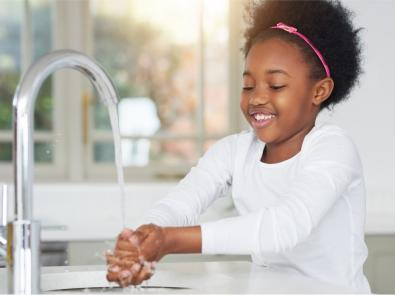 Young girl washes her hands over a sink