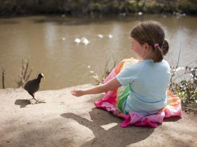 Girl sits by a river looking at bird