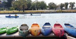 Canoes of different colours in the foreground, waiting to be taken into the water.